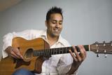 Mixed race man playing guitar