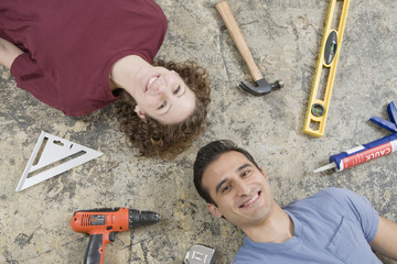 Couple laying on floor with tools