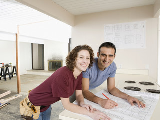 Couple looking at blueprint in kitchen