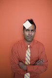 Mixed race businessman with sticky note on forehead