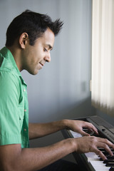 Mixed race man playing electric keyboard
