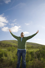 Mixed race man in field with arms outstretched