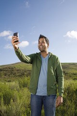 Mixed race man taking photo with cell phone