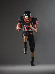 Mixed race football player running with football