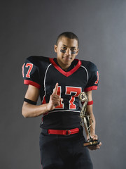 Mixed race football player holding trophy and gesturing