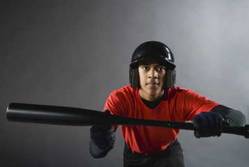 Mixed race baseball player ready to bunt with baseball bat