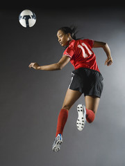 Mixed race soccer player in air with soccer ball
