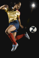 Mixed race soccer player kicking ball in mid-air