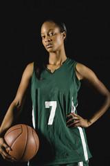 Mixed race basketball player holding basketball