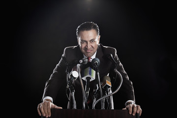 Hispanic man standing at podium with microphones