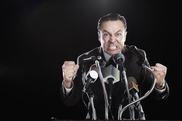 Angry Hispanic man gesturing with fists at podium with microphones