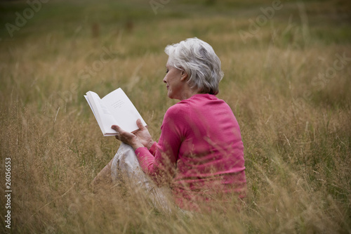 A senior woman sitting on the grass, reading a book, rear view