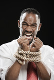 Angry African man with wrists bound by rope