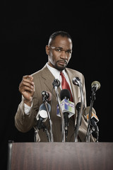 African man standing at podium with microphones