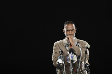 African man looking pensive at podium with microphones