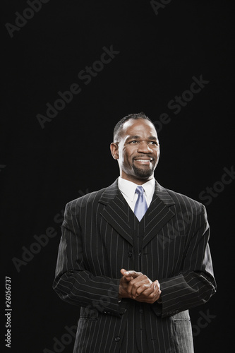 African man in suit smiling with hands clasped