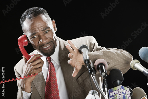 Worried African man talking on telephone at podium with microphones
