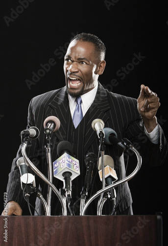 Angry African man gesturing at podium with microphones