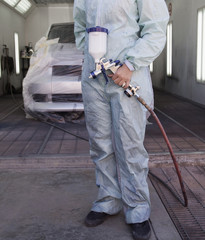Worker holding painting equipment in auto body shop