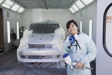 Hispanic worker preparing to paint car in auto body shop