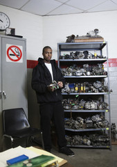 Mixed race man holding engine part in office