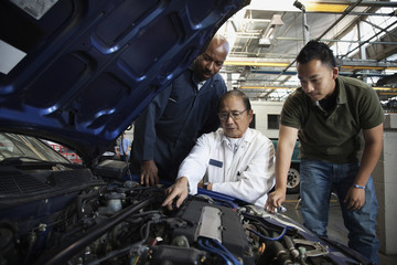 Mechanics examining engine of car