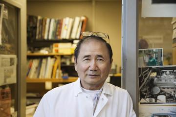 Japanese mechanic standing in office doorway