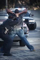 Policewoman frisking man