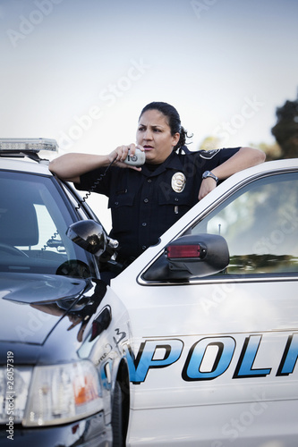 Hispanic policewoman talking on CB radio