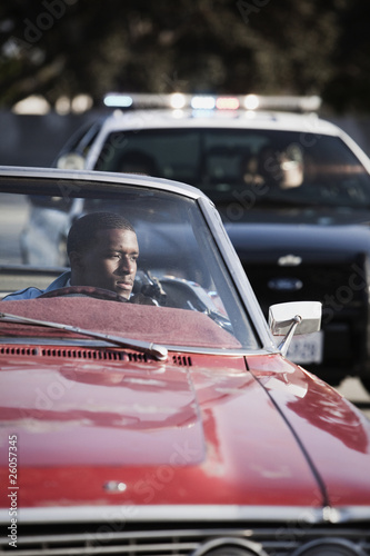 African man in convertible being pulled over by police