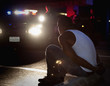 Police shining lights on handcuffed African man sitting on curb