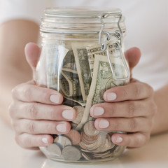Woman holding jar with money