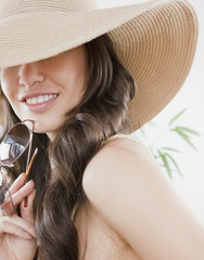 Mixed race woman wearing sun hat and holding sunglasses