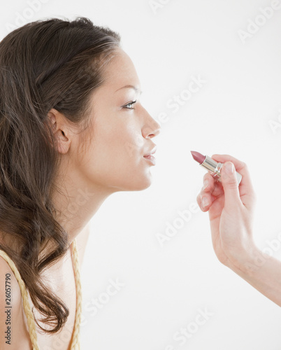 Lipstick being applied to lips of mixed race woman