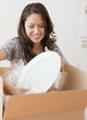Mixed race woman unpacking dishes