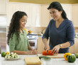 Hispanic mother and daughter slicing vegetables