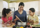 Hispanic mother cooking with daughter and son