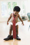 African toddler wearing father's shoes and tie