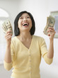 Smiling Filipino woman holding money and looking up