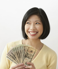 Filipino woman holding money and smiling