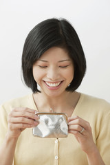 Filipino woman looking into wallet and smiling