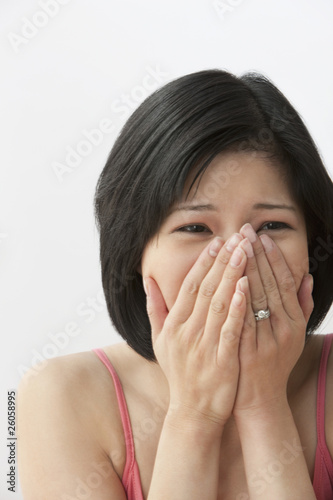 Filipino woman covering face with hands