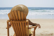 Mixed race woman relaxing in chair on beach