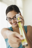 Mixed race woman holding tape measure