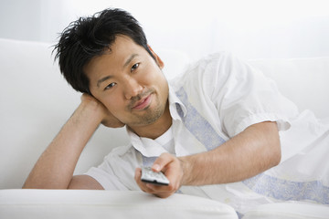 Asian man holding remote control