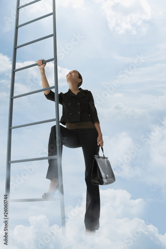 Mixed race woman climbing ladder in clouds