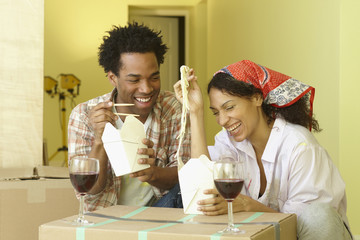 African couple eating take-out and drinking wine on cardboard boxes