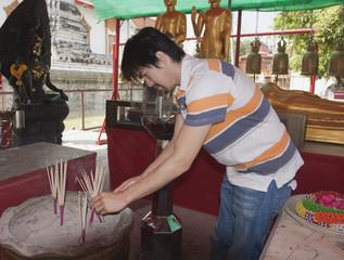 Asian man placing prayer sticks in sand