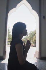 Asian woman praying in temple