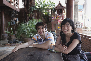 Asian couple sitting at patio table
